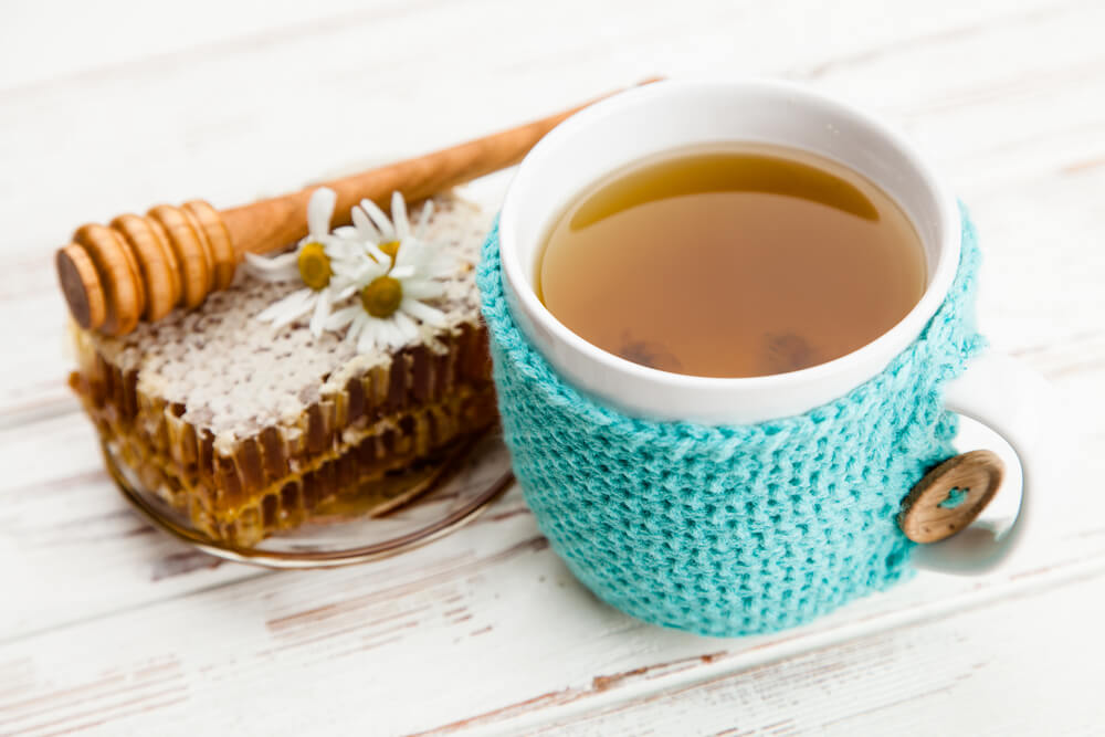 Honeycomb and chamomile tea on white wooden table