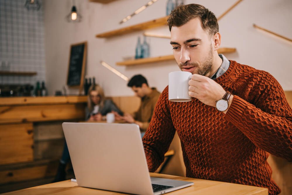 man drinking coffee in a Cafe looking at his laptop