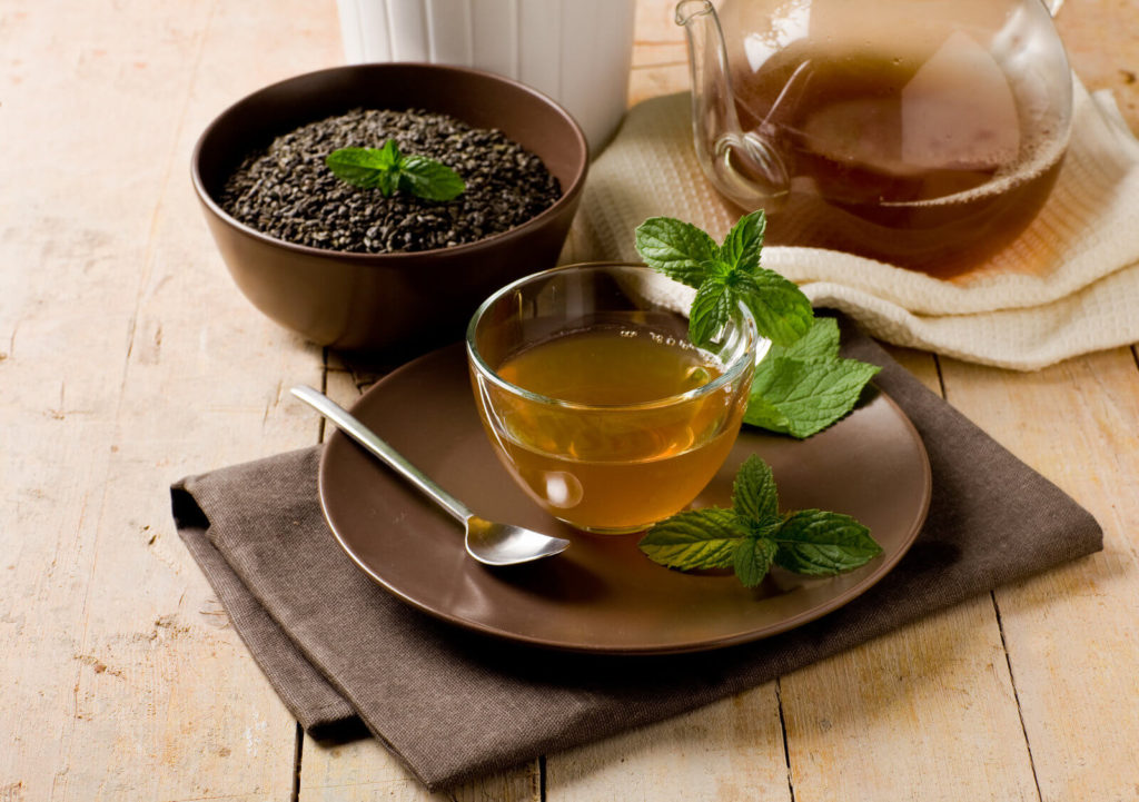 green mint tea in glass cup on wooden table