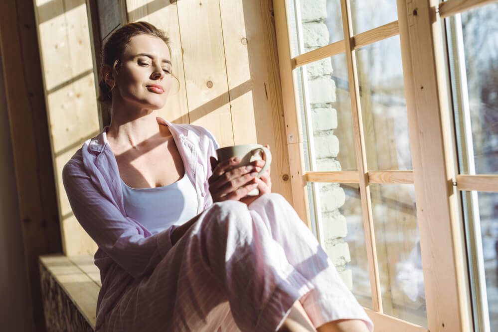 woman enjoying her cup of coffee while sitting near a window