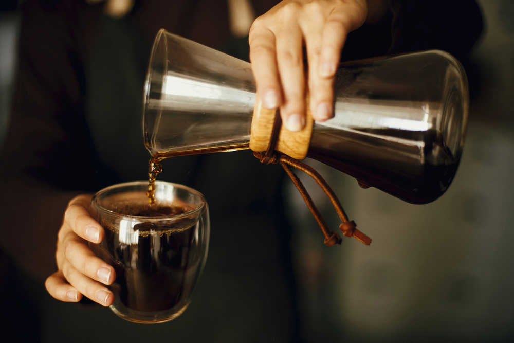 person pouring fresh black aromatic coffee