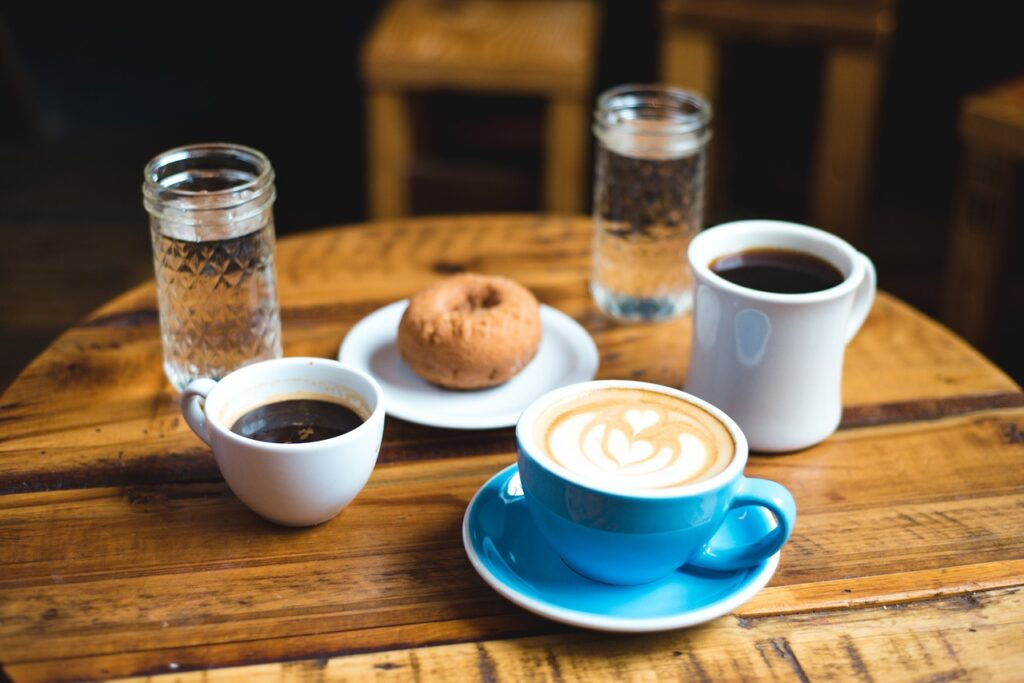 different sizes of coffee cups filled with coffee and a donut for breakfast