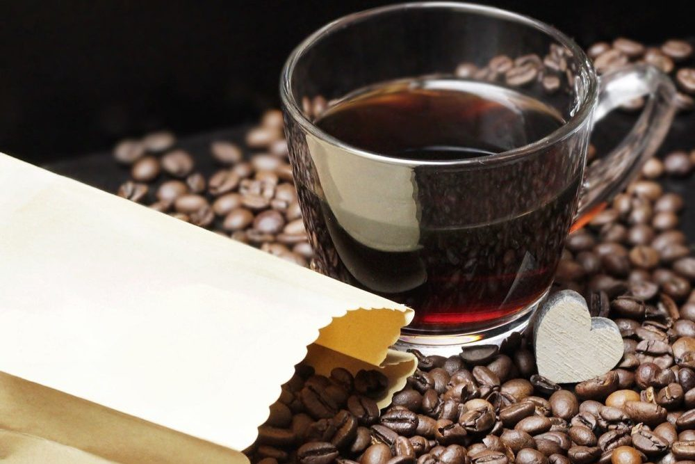 12 Ways To Make Coffee Less Acidic - a cup of coffee above the coffee beans