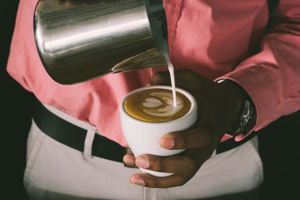 pouring milk on a coffee