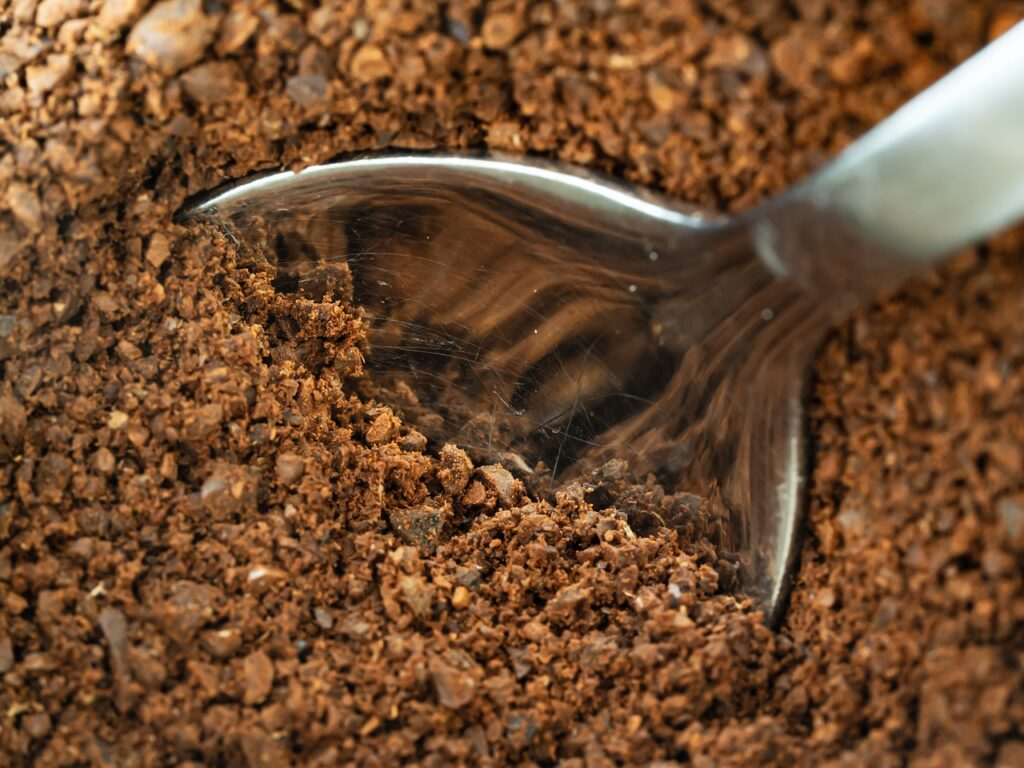 trying to scoop a tablespoon of coarse coffee grounds