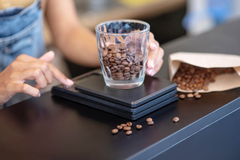 weighing whole beans of coffee