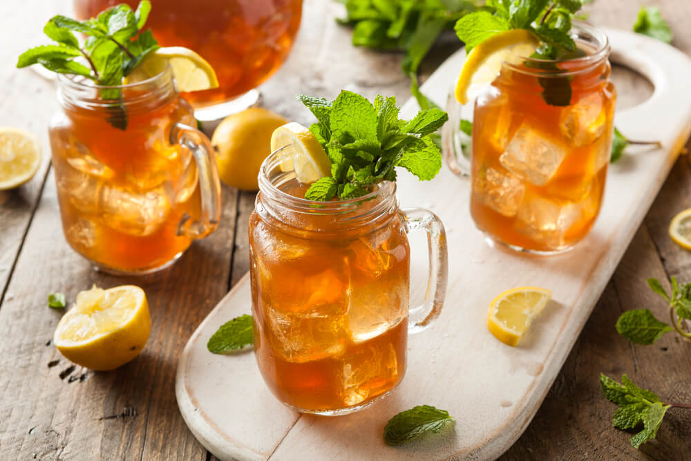 boozy sweet tea - homemade iced tea filling three large containers
