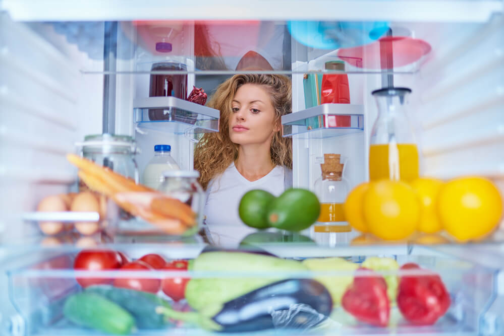 Woman standing in front of fridge full of groceries items and drinks - how long does tea last in the fridge