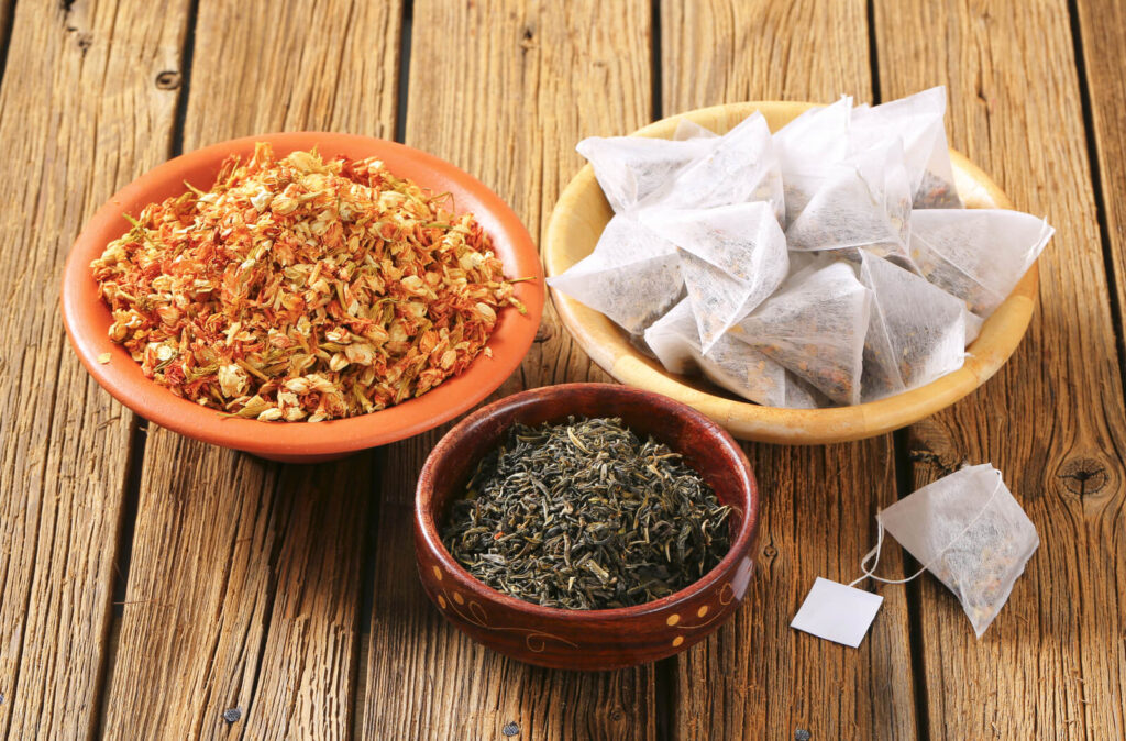 Dried jasmine leaves and flowers and pyramid tea bags