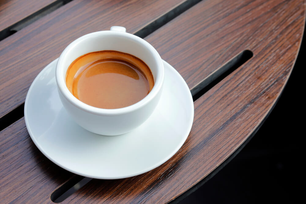 espresso coffee serve on top of a wooden table