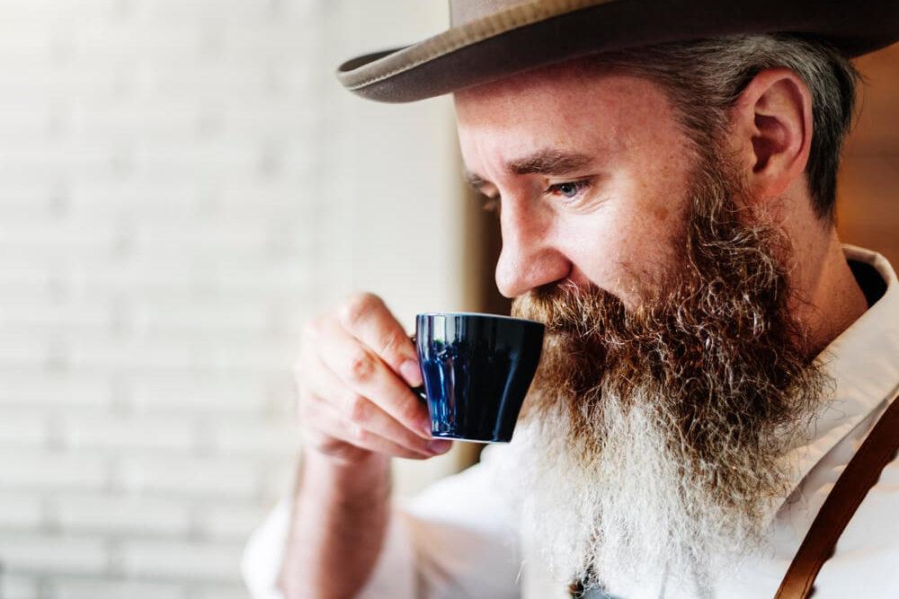 bearded man enjoying his coffee