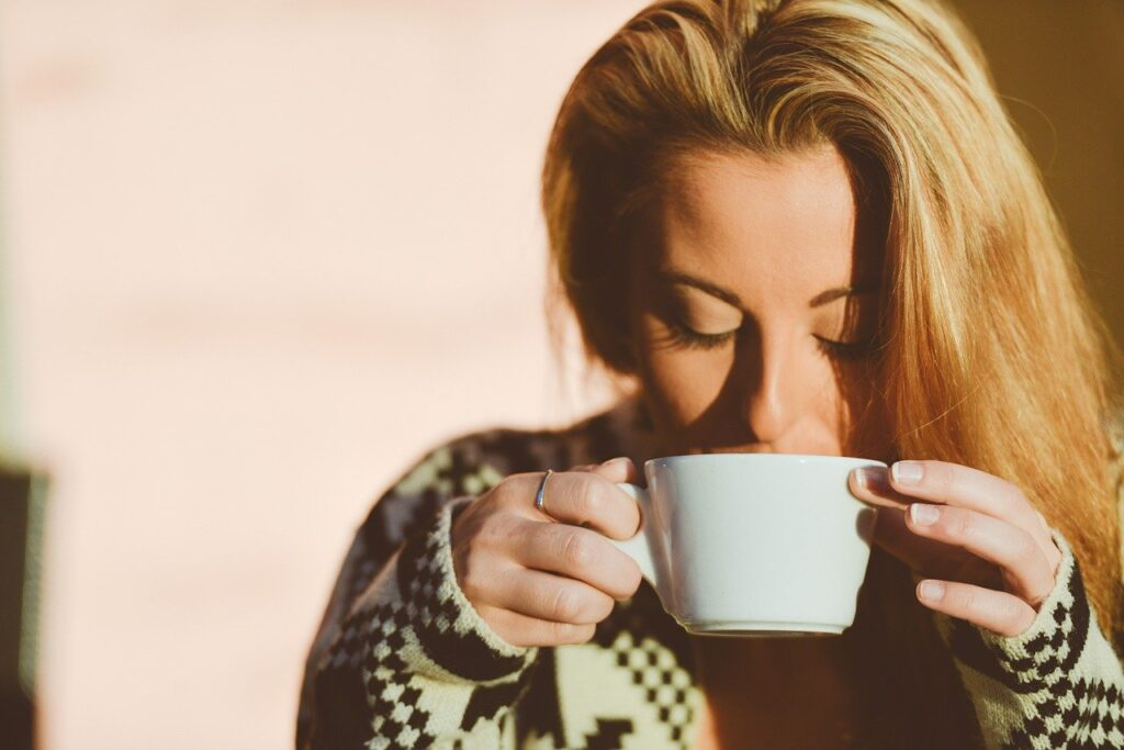 woman drinking her coffee outside her house