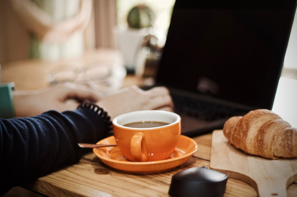 person using a laptop with a coffee and bread beside