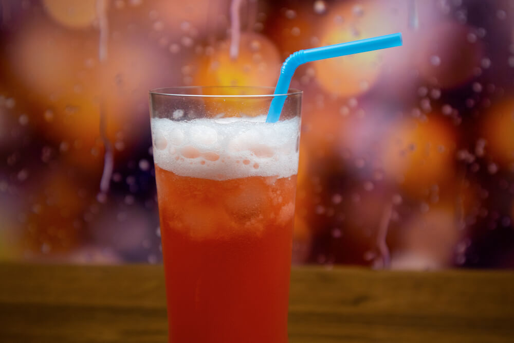 Bahama Mama cocktail in highball glass with ice and blue straw
