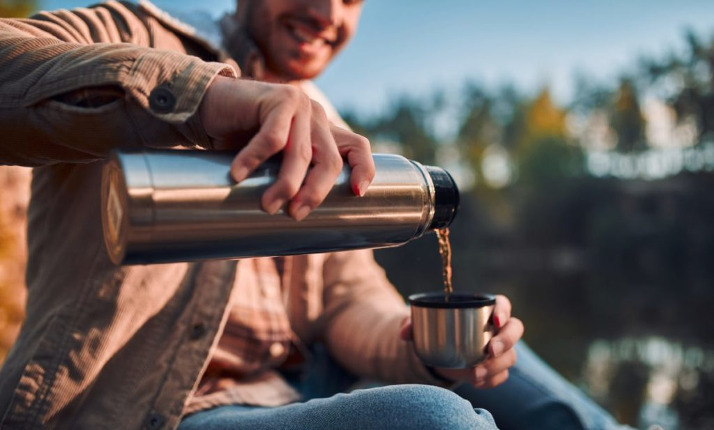 man pouring coffee in a coffee thermos