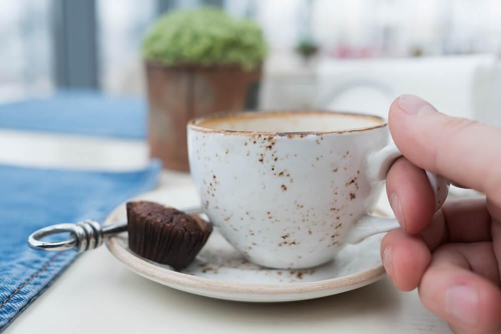 a hand holding a scratched coffee mug