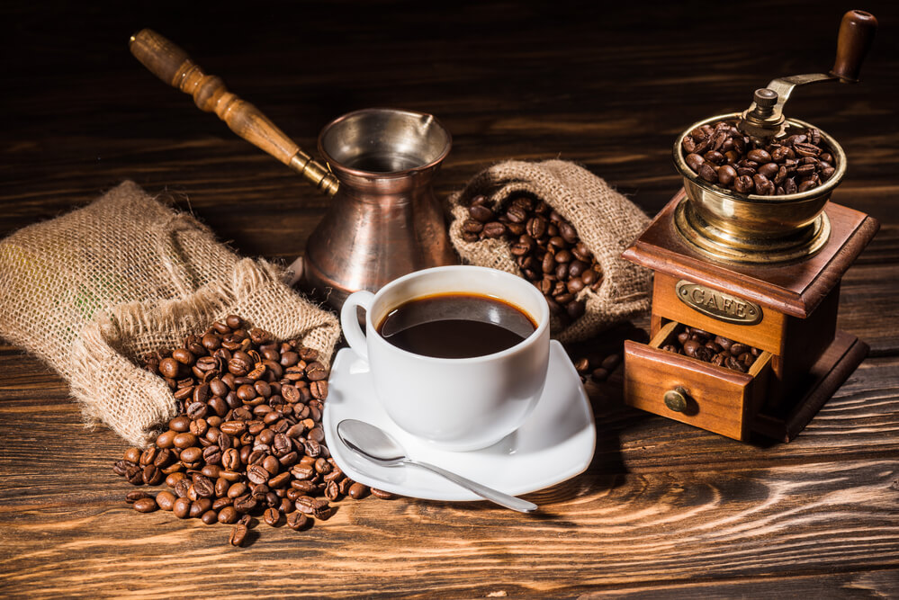 cup of coffee with coffee beans and a coffee pot