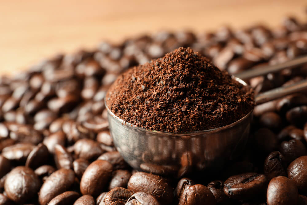 ground coffee surrounded by coffee beans