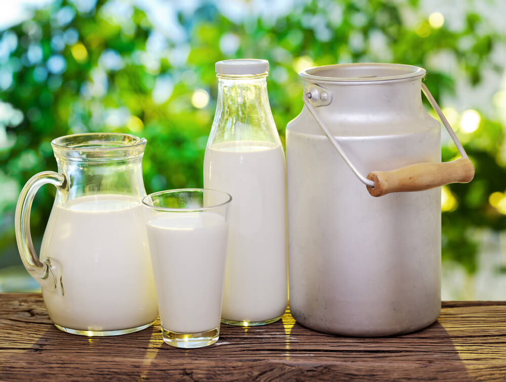 three bottle of milk and a container of old milk