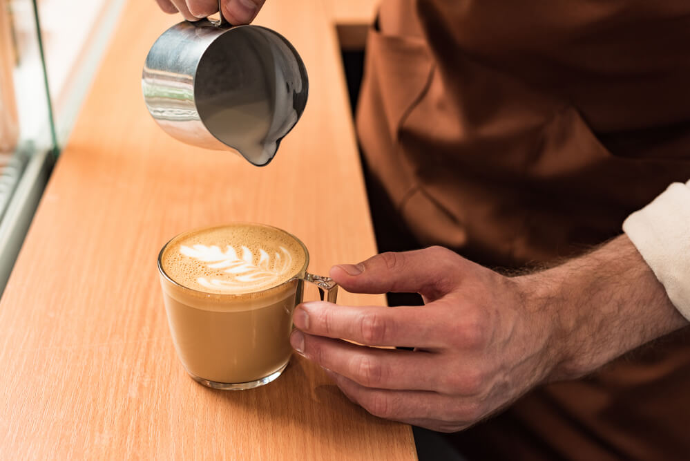 a hand pouring a milk to a coffee