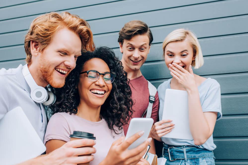 friends checking their cellphones while having their coffee break