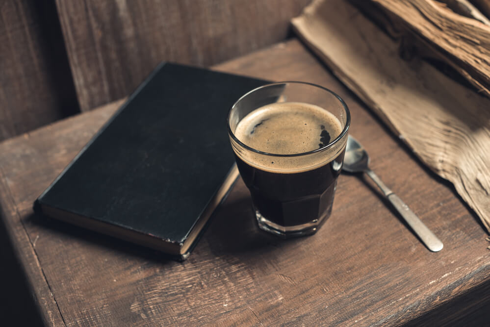 old look of a coffee beside a journal notebook - why is coffee called joe