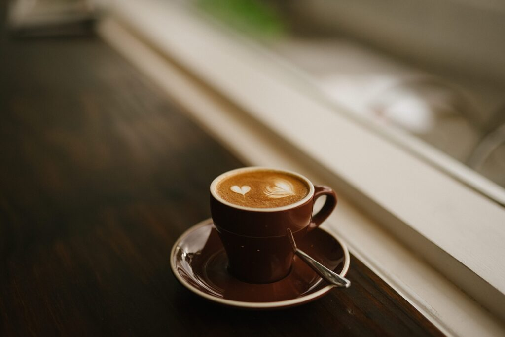 freshly brewed cappuccino coffee on a brown cup
