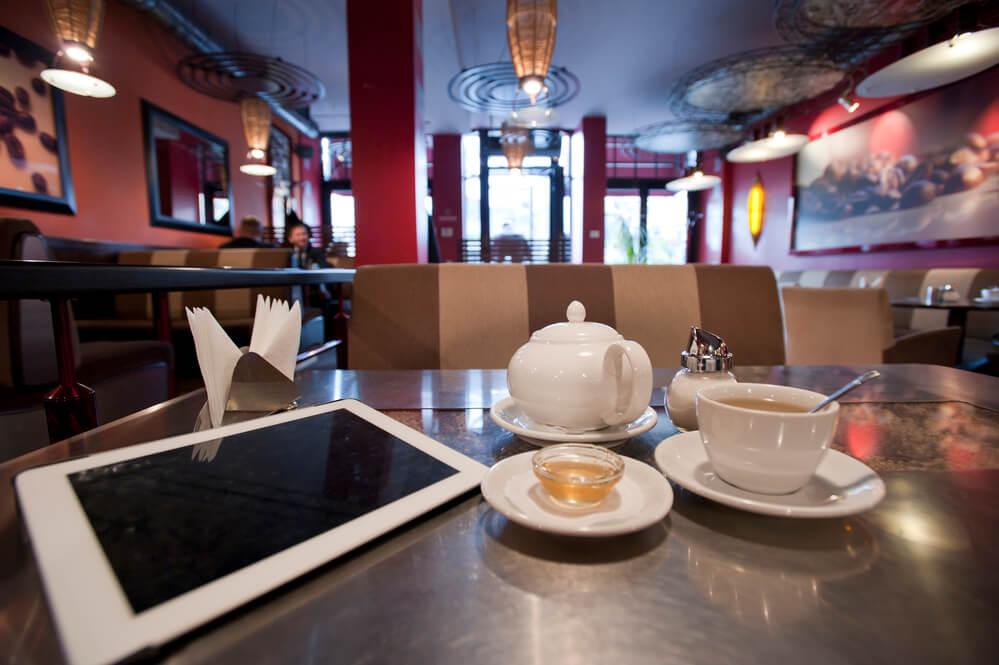 an iPad and a coffee on a table inside a coffee shop