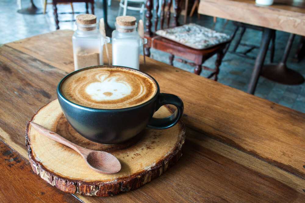 a cup of coffee at the top of a wooden table
