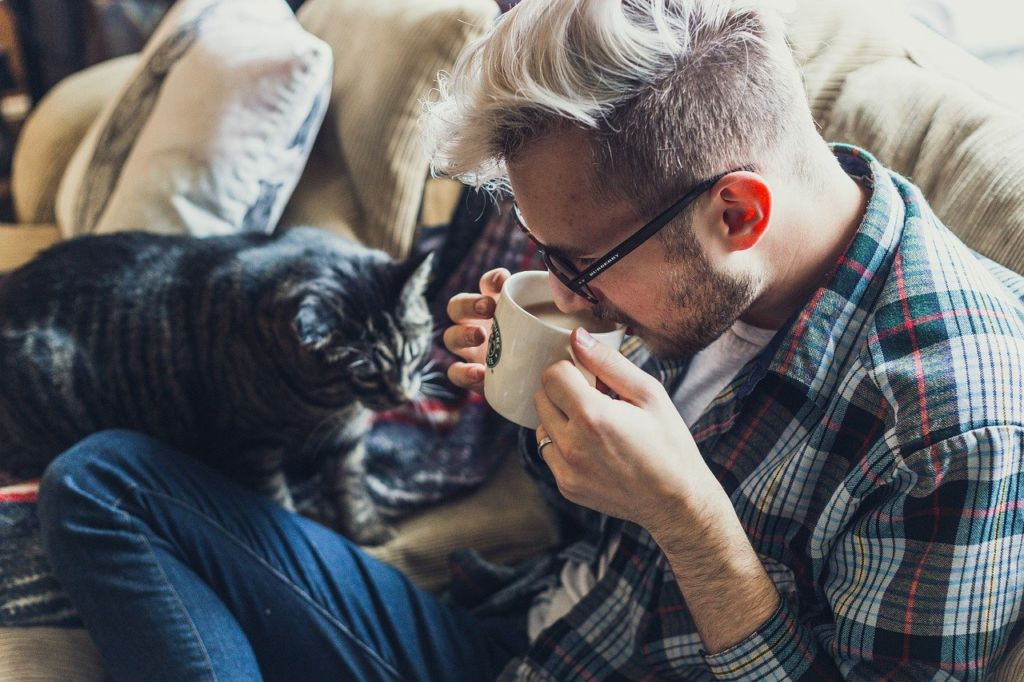 young bearded man drinking coffee with cinnamon in a couch