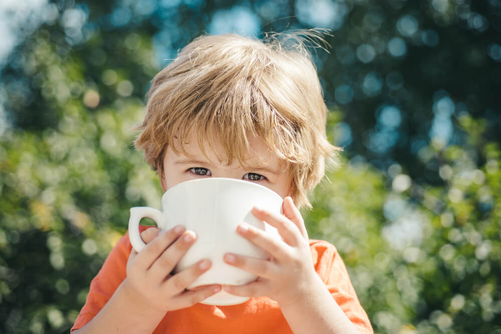 A little toddler is sitting in a garden and is drinking from coffee cup