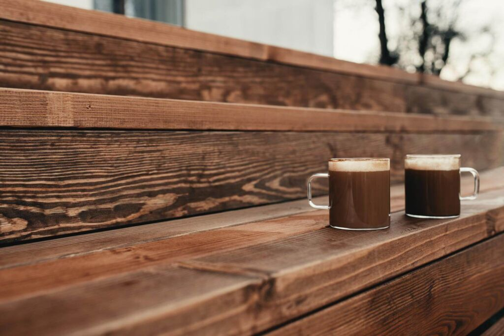 Two cups of coffee in the wooden brown terrace background - Acidic Vs Bitter Coffee