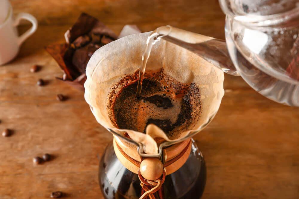 Preparing of tasty coffee in chemex on table