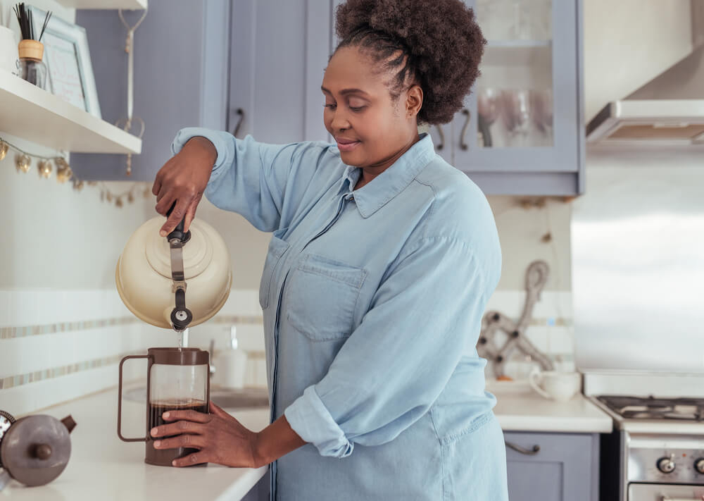 A woman preparing French press coffee.