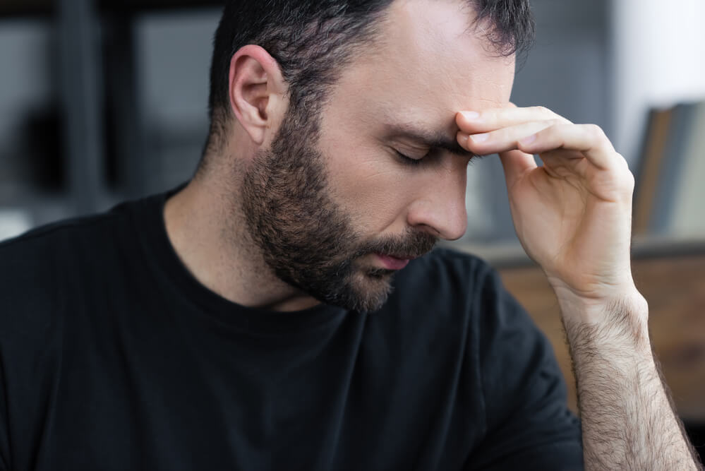 bearded man with eyes closed holding his forehead - Does Coffee Get Rid Of Headaches