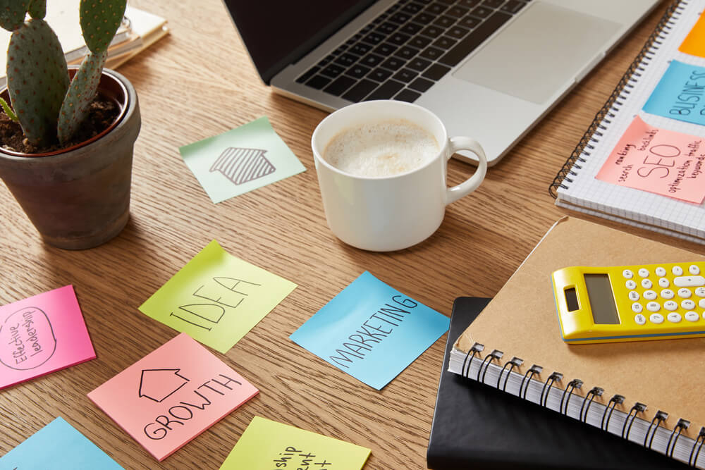 Note paper sheets with business strategy, calculator and laptop - Coffee shop marketing plan