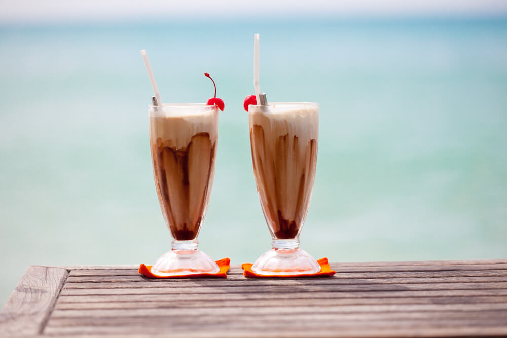 two cups of long island ice coffee on the beach