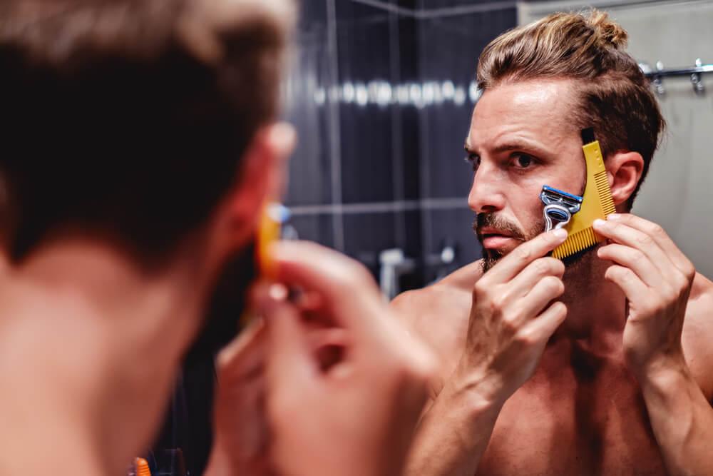 Man shaving his beard in the bathroom