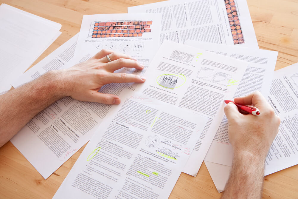 reviewing scientific papers on a table