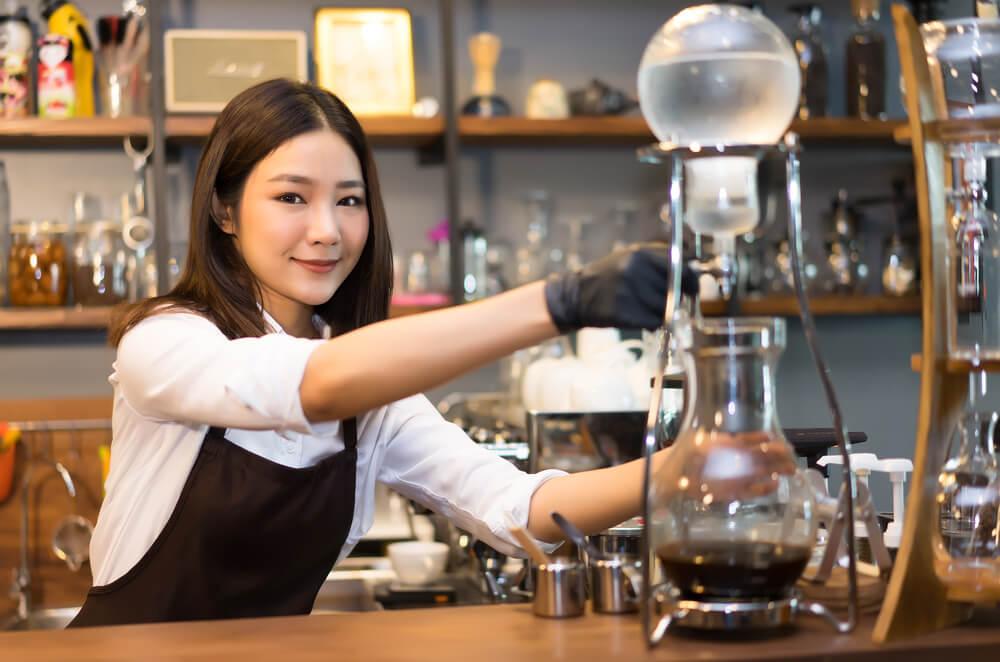 beautiful barista making iced slow drip coffee