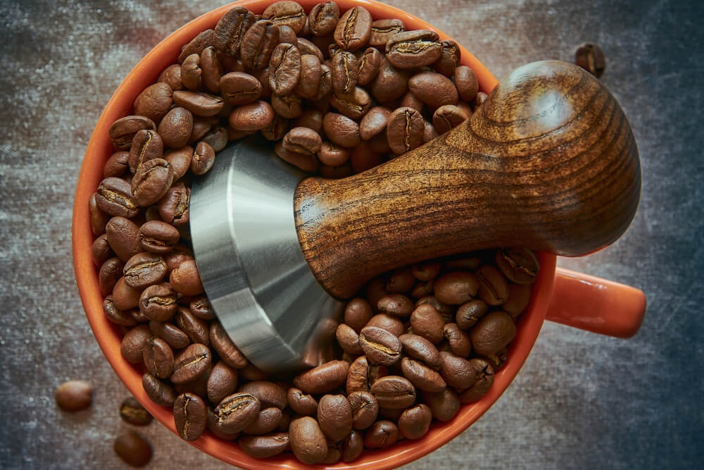 Coffee tamper in a cup with coffee beans
