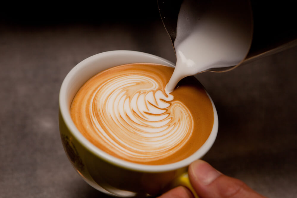 almond milk poured to a cup of coffee
