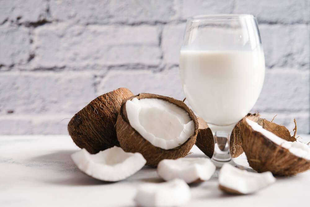 coconut milk with broken coconut beside it