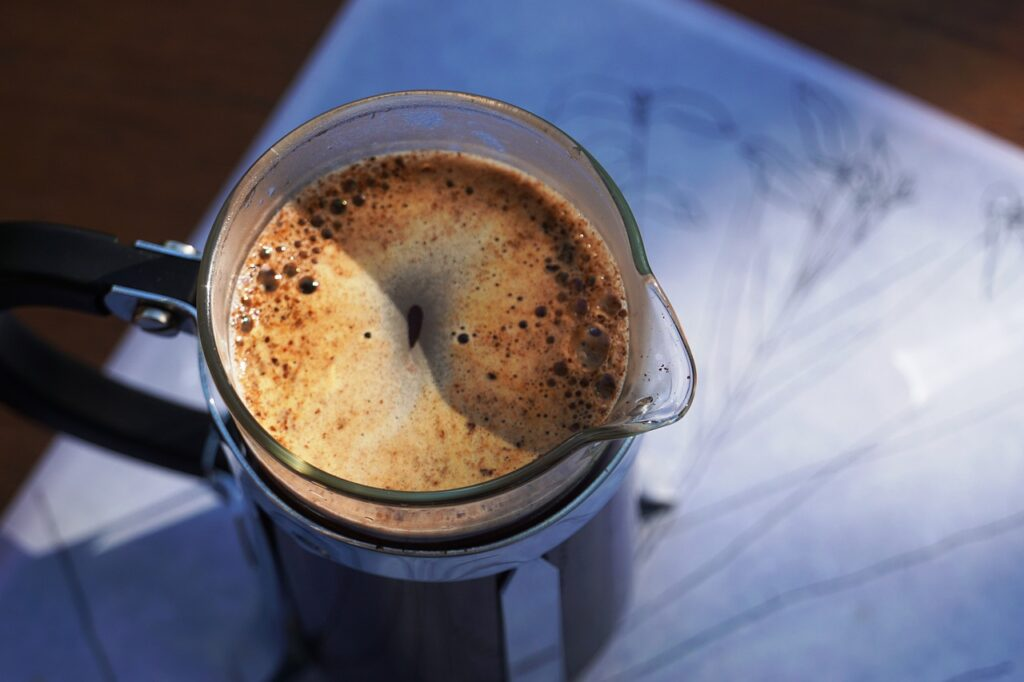 a freshly brewed coffee on a french press. bubbles are visible at the top