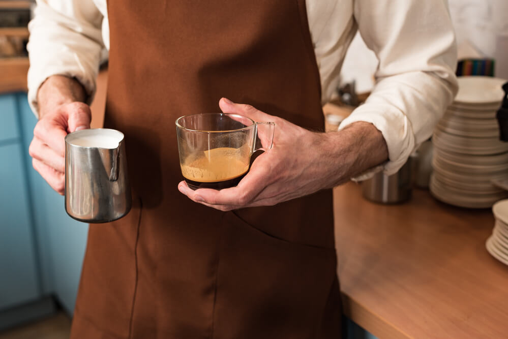 a man holding a cup of coffee and a milk