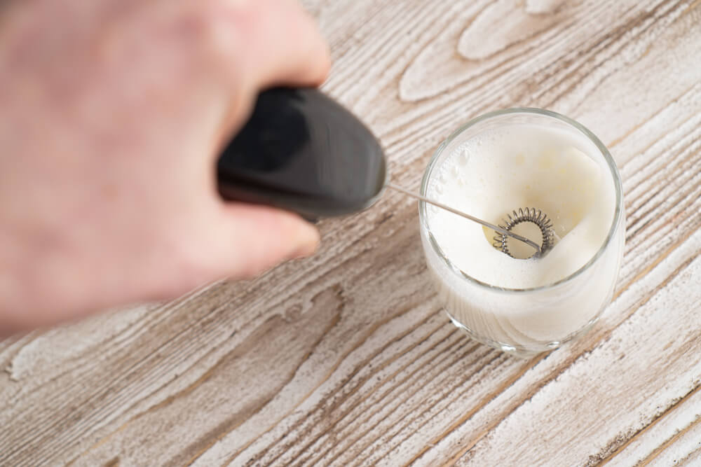 making milk froth in a glass using an electric milk frother