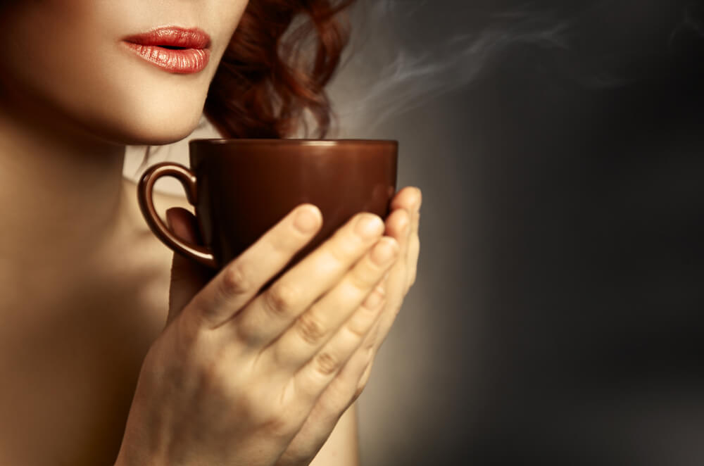 woman about to drink her coffee