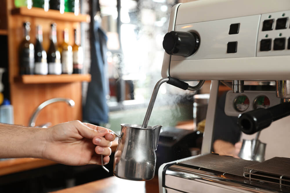 Barista steaming milk in a metal jug with coffee machine wand at the bar counter - does humidity affect milk frothing