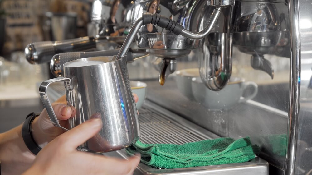 Barista steaming milk in frothing jug - how do milk frothing jugs work