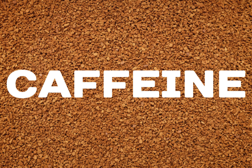 CAFFEINE text written over background of instant coffee granules